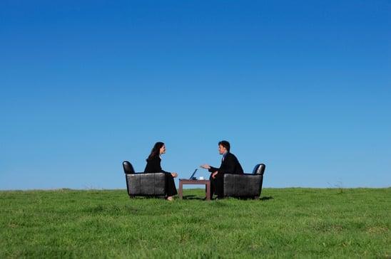 two-business-people-sitting-in-field-talking.jpg