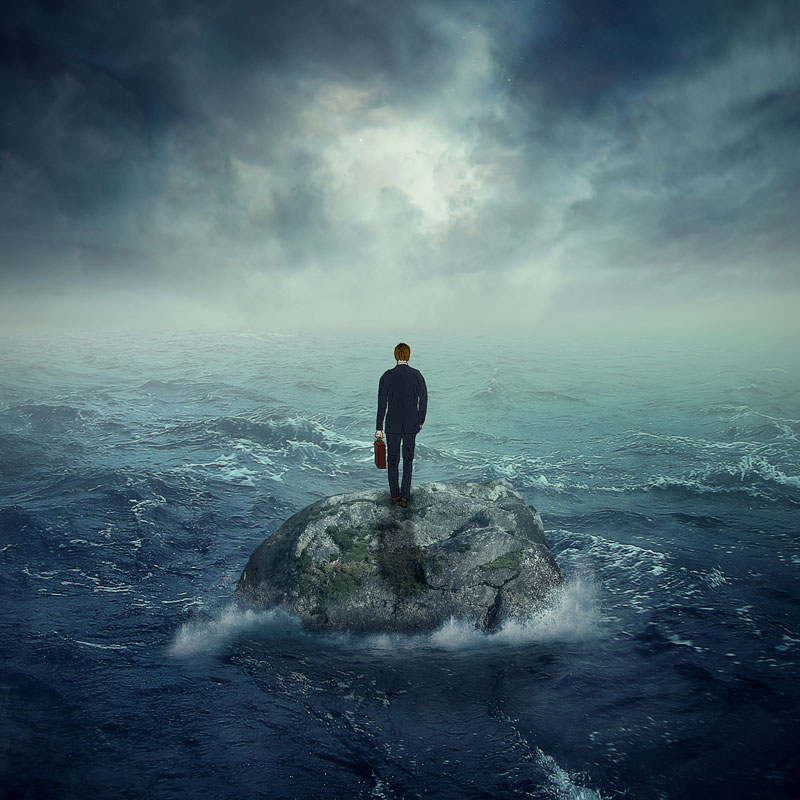 man-standing-on-rock-in-stormy-sea